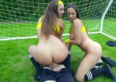 Two hot sluts are at a football field, playing with some large balls