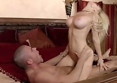 Blonde with big fake boobs is on the bed where she is getting fucked