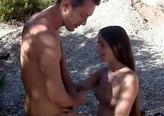 Brunette woman is undressed outside and she gives a blow job